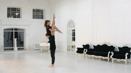 pilates : Girl with a guy rehearsing dance in the hall, gymnastic dance in the dance hall