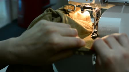 döner : A woman working on a sewing project as she cuts fabric and sews it on a machine. sewing machine close up A hand of a dressmaker supporting a cloth while sewing on a machine.