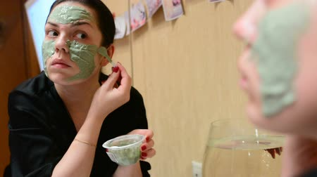 bahno : Young girl applying cosmetic mask of green clay in the room in front of the mirror