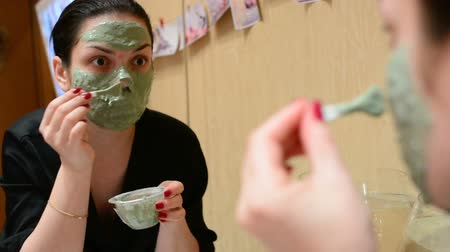 clay mask : Young girl applying cosmetic mask of green clay in the room in front of the mirror