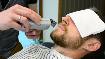 trim : Mens hairstyling and haircutting in a barber shop or hair salon. Grooming the beard. Barbershop. Man hairdresser doing haircut beard adult men in the mens hair salon. Hairdressers in the workplace