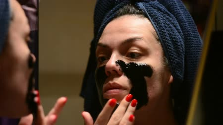 descamação : A woman looks after the skin of the face using a professional cosmetic black mask. Skin cleansing, pores with a black mask.