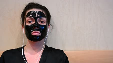 sheet music : Young woman doing facial black mask with purifying mask on her face and listening to music