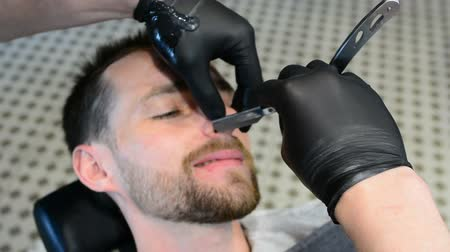 barber equipment : Beard cut with straight razor shave. Close up of shaving beard. Male beard style. Barber shaving hipster man face Stock Footage