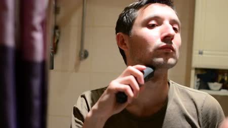 zęby : beauty, grooming and people concept - young man looking to mirror and shaving beard with trimmer or electric shaver at home bathroom