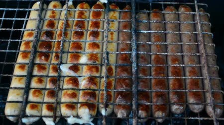 párek v rohlíku : Barbecue browned sausages on the hot grill, a person turn and put upon brazier