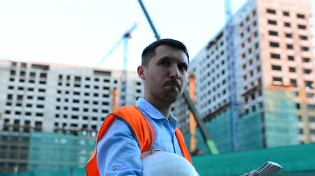workman : Adult engineer. Writes a message or checks a drawing. Against background is building. Builders are building a modern residential building of glass and concrete.