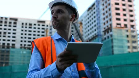 munkás : Adult engineer. Writes a message or checks a drawing. Against background is building. Builders are building a modern residential building of glass and concrete.