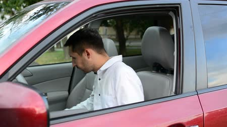 itself : Young driver being impatient, waiting inside his car and showing signs of frustration.