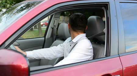 országúti : Young driver being impatient, waiting inside his car and showing signs of frustration.