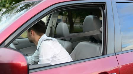 yönlendirmek : Young driver being impatient, waiting inside his car and showing signs of frustration.