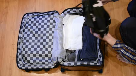 materiaŁ : Top view travel concept of man sorting and packing his clothes in suitcase