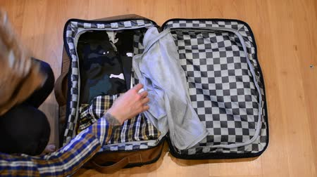 coisas : Top view travel concept of man sorting and packing his clothes in suitcase