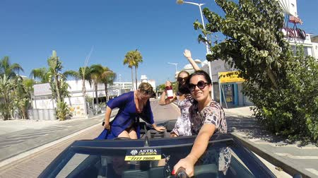 kabriolet : CYPRUS, SENTEMBER 2018: Girls Enjoy A Ride In A Convertible With Their Arms Raised Wideo