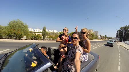 cabriolet : CYPRUS, SENTEMBER 2018: Girls Enjoy A Ride In A Convertible With Their Arms Raised Stock Footage