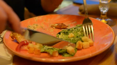 grzanki : Macro closeup of caesar salad on plate with red tongs, parmesan cheese, dressing, tongs, people moving, eating in background Wideo