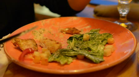 chicken recipes : Macro closeup of caesar salad on plate with red tongs, parmesan cheese, dressing, tongs, people moving, eating in background Stock Footage