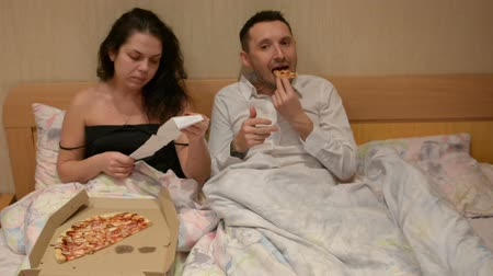 fast food : Couple in bed eating pizza delivery