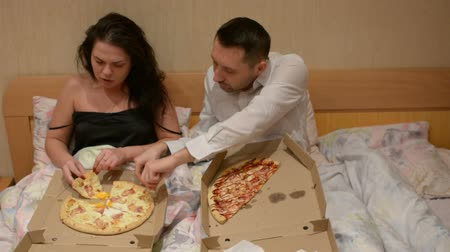 linen : Couple in bed eating pizza delivery