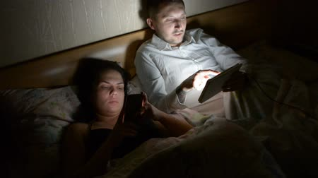 linen : Couple with smartphone and tablet lying on bed
