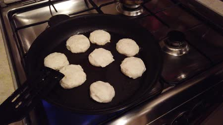 twaróg : Young woman makes cottage cheese pancakes at kitchen stove