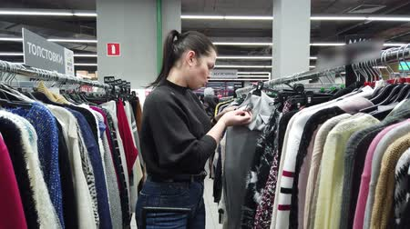 消費者運動 : Young women shopping in fashion mall, choosing new clothes, looking through hangers with different casual colorful garments on hangers