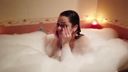 rosa : Attractive young woman taking a bubble bath by burning candles