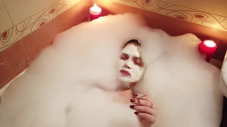 duygusallık : Girl with clay mask on face smoking a smokes cigarettes in bathroom filled with foam