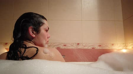 dinlenmek : Attractive young woman taking a bubble bath by burning candles