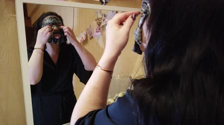 bőrápolás : Young woman doing facial mask on her face Stock mozgókép