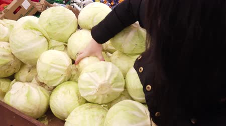 comprador : Young woman chooses cabbage on store shelves.