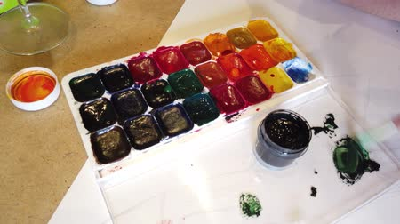 oy : Woman hands painting colorful rainbow. Set for painting with various brushes, paints and crayons. Top view