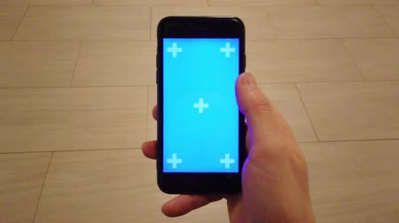 telefonkönyv : Young Man is Holding Smartphone. Using touchscreen touch, tap, swipe hand gestures on blue screen. Stock mozgókép