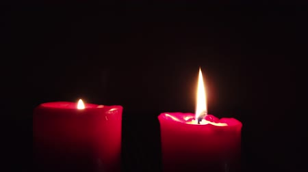 knot : Burning red candle with flickering flame on dark background.