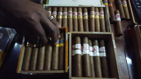 barganha : HAVANA, CUBA - APRIL 2019: Customers choose cigars in the store. Cuban cigars in Havana city store