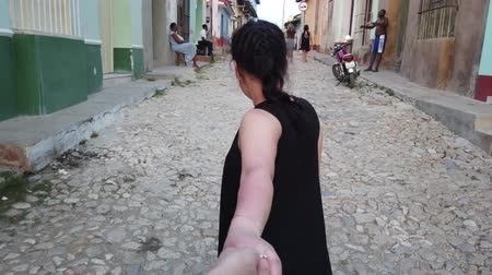 ведущий : Trinidad, Cuba - April 2019: Young couple holding hands up leading down girlfriend walking down city street in Trinidad, Cuba. POV travel concept