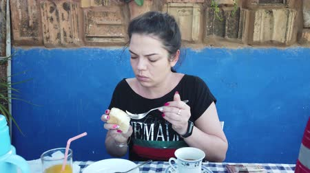 aromatik : Beautiful young woman smokes a cigarette. Girl having Breakfast on veranda. Stok Video