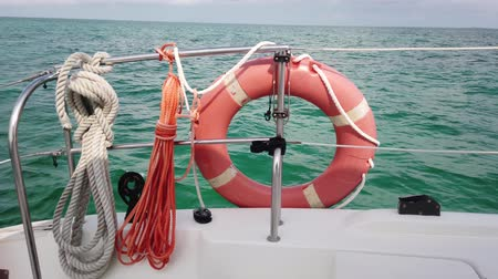 rescuer : Red life buoy over blue calm sea water background. Lifebuoy on the boat