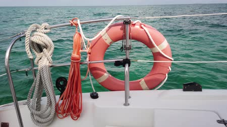 sos : Red life buoy over blue calm sea water background. Lifebuoy on the boat