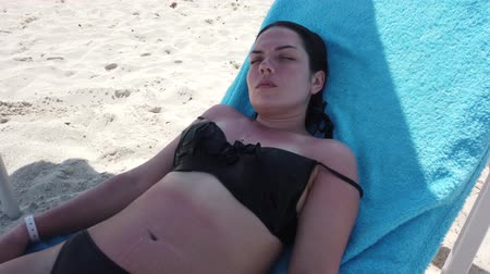 благополучия : Vacation beach travel in bikini. Sunbathing beautiful girl lying in sun lounger at luxury hotel resort. Paradise beach. Стоковые видеозаписи