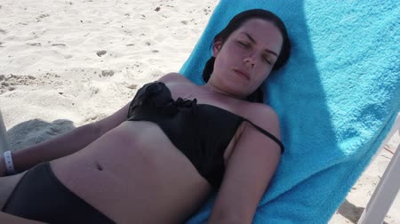 çare : Vacation beach travel in bikini. Sunbathing beautiful girl lying in sun lounger at luxury hotel resort. Paradise beach. Stok Video