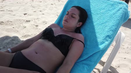 genç yetişkinler : Vacation beach travel in bikini. Sunbathing beautiful girl lying in sun lounger at luxury hotel resort. Paradise beach. Stok Video
