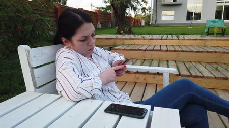 tipo : Woman use of mobile phone and sit on the bench in the yard home Vídeos