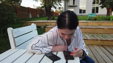 banc : Woman use of mobile phone and sit on the bench in the yard home Vidéos Libres De Droits