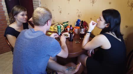 bavorské : MOSCOW, RUSSIA - JULY, 2019: Company of friends resting at home. Drink beer and cider, eat seeds. Dostupné videozáznamy