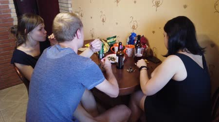 ziyafet : MOSCOW, RUSSIA - JULY, 2019: Company of friends resting at home. Drink beer and cider, eat seeds. Stok Video