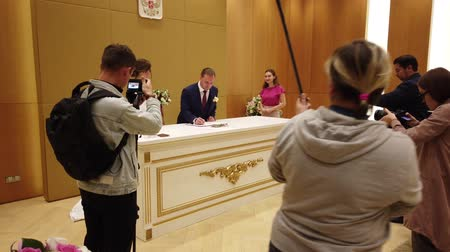 enjoys : MOSCOW, RUSSIA - AUGUST, 2019: The wedding ceremony, the bride and groom sign.