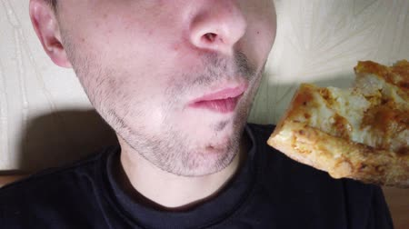kalori : Man eats fast food biting pizza slice extreme close up Stok Video