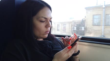 vagão : Beautiful young girl seats in the wagon of the train and use the smartphone, texting messages to friends and looking in the window