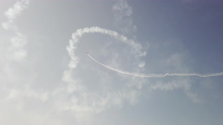 aircrew : An airplane in the sky shows aerobatics figures